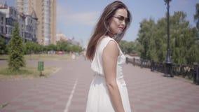 画象迷人的少女佩带的太阳镜和走一件长的白色夏天时尚的礼服户外 a休闲  影视素材