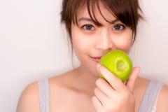 画象迷人的美丽的健康妇女 有吸引力的女孩举行绿色苹果 吃果子的俏丽的亚洲妇女爱 图库摄影