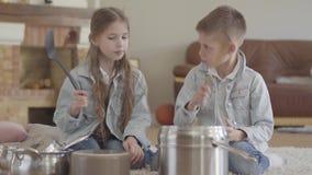 画象逗人喜爱的可爱的兄弟和扮演音乐家的姐妹孪生打罐和盘与大匙子和笑 影视素材