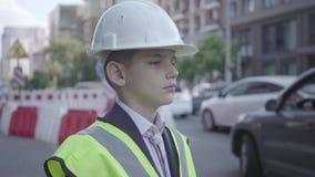 画象逗人喜爱的小男孩佩带的西装和安全设备和建设者在一条繁忙的路的盔甲身分在a 影视素材
