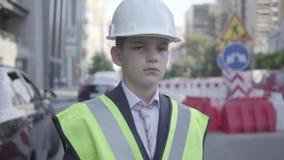 画象逗人喜爱的小男孩佩带的西装和安全设备和建设者在一条繁忙的路的盔甲身分在a 股票视频