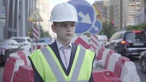 画象逗人喜爱的小男孩佩带的西装和安全设备和建设者在一条繁忙的路的盔甲身分在a 股票录像