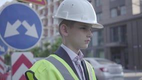 画象逗人喜爱的小男孩佩带的西装和安全设备和建设者在一条繁忙的路的盔甲身分  股票视频