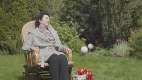 画象逗人喜爱的愉快的成熟妇女坐享用太阳的摇椅的草坪 与近郁金香的篮子 股票视频