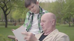 画象逗人喜爱的爷爷和可爱的孙子在公园坐长凳,读男孩的老人书 影视素材