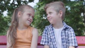 画象逗人喜爱的男孩和女孩坐摇摆关闭在公园,跳舞,获得看的乐趣秘密审议 两三 股票视频