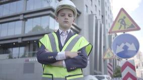 画象逗人喜爱的矮小的成功的男孩佩带的西装和安全设备和建设者在繁忙的盔甲身分 影视素材