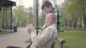 画象逗人喜爱的祖父和可爱的孙子在公园坐长凳,读男孩的老人书 影视素材