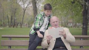 画象逗人喜爱的祖父和可爱的孙子在公园坐长凳,读男孩的老人书 股票录像