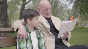 画象逗人喜爱的祖父和孙子在公园坐长凳,读男孩的老人书 影视素材
