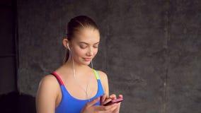 画象面孔少妇佩带的耳机听在健身房关闭的音乐运动员微笑锻炼女性健康身体 股票录像