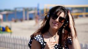 画象,佩带大黑耳机的太阳镜的美丽的女孩,听到从智能手机的音乐,在海滩,  影视素材
