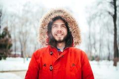 画象,微笑与胡子的一个年轻人时髦地加工好的人的特写镜头在有一张敞篷和毛皮的一件红色冬天夹克穿戴了在他的 免版税库存图片