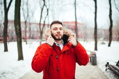 画象,微笑与胡子的一个年轻人时髦地加工好的人的特写镜头在有一张敞篷和毛皮的一件红色冬天夹克穿戴了在他的 免版税库存照片