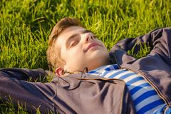 画象,逗人喜爱的青少年的男孩听的音乐,躺下在新鲜的绿草 库存照片