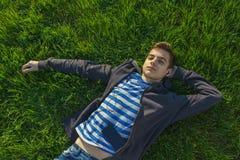 画象,逗人喜爱的青少年的男孩听的音乐,躺下在新鲜的绿草 库存图片