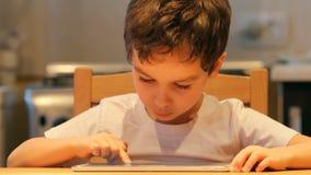 画象:一个逗人喜爱的小孩在家使用一台片剂个人计算机在桌 衣裳:白色衬衣 图库摄影