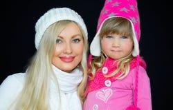 画象 妈妈和女儿,被编织的帽子的,在黑背景 愉快的家庭、微笑和喜悦 免版税库存图片