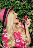 画象 帽子的美丽的白肤金发的女孩笑 在他的手上拿着花 在露天 在她的绿色叶子后 它是illu 免版税库存照片