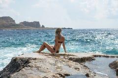 画象 年轻女人坐一个大岩石和神色入距离海上 有选择性的软的焦点 几天愉快的夏天 Balos 库存照片
