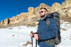 画象A有胡子的行家有背包的和有一个大背包的太阳镜的在他的肩膀站立用棍子 免版税库存图片
