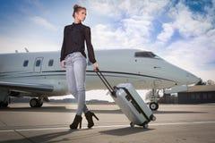 留下一架公司喷气机飞机的行政女商人 免版税库存照片