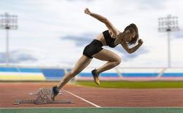 留下出发台的妇女短跑选手在运动轨道 图库摄影