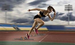 留下出发台的妇女短跑选手在运动轨道 库存照片
