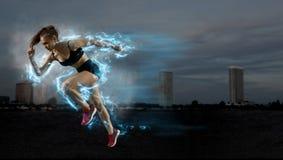 留下出发台的妇女短跑选手在运动轨道 免版税图库摄影