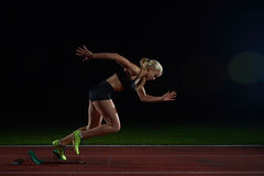留下出发台的妇女短跑选手 免版税库存图片