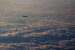 留下转换轨迹的飞机被看见从另一架飞机在云彩一张喜怒无常的地毯在日落期间 库存图片