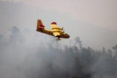 留下水的飞机消防队员反对火 免版税库存图片