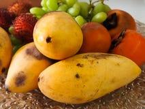 番木瓜柿子果子和葡萄在盘子说谎 免版税库存图片