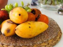 番木瓜柿子果子和葡萄在盘子说谎 免版税库存照片