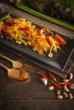 番木瓜沙拉索马里兰在那里木桌安置的方形的黑色的盘子的胃泰语是豆,烤鱼,大蒜,辣椒匙子和 库存图片