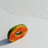 番木瓜,手,切片,热带水果,海,沙子 免版税库存图片