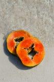 番木瓜,手,切片,热带水果,海,沙子 免版税图库摄影