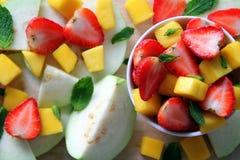 番石榴、芒果和草莓与薄菏叶子在木背景 免版税库存照片