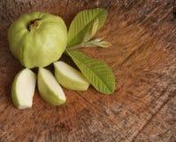 番石榴与叶子的果子和番石榴切片在木背景 库存照片