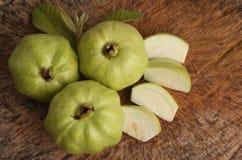番石榴果子和切片与叶子在木背景 免版税库存图片