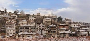 番红花城多雪的冬时的Karabuk土耳其房子和小山全景 库存照片