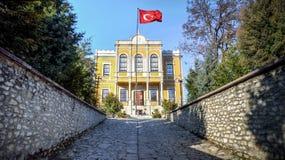 番红花城,土耳其- 2013年1月20日:历史政府机关大厦在有土耳其旗子的番红花城村庄 库存照片