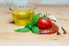 番茄酱蕃茄蓬蒿橄榄油草本大蒜板黑胡椒成份 免版税库存照片