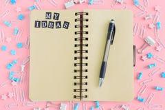 疏散办公用品在笔记本附近说谎混乱 在春天的笔记薄有棕色页的 我的题字 免版税库存照片