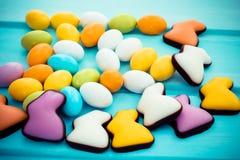 疏散复活节五颜六色的甜巧克力小鸡蛋用在绿松石背景的糖果兔子 免版税库存照片