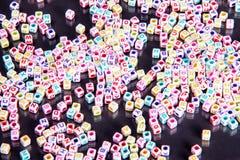 疏散多颜色字母表在反射性黑背景成串珠状 免版税图库摄影