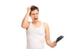 疏松头发和拿着发刷的恼怒的人 免版税库存图片