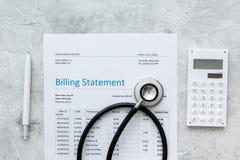 医疗保健与医生` s听诊器和笔的布告声明在石背景顶视图 免版税库存照片