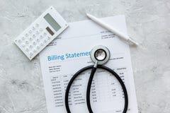 医疗保健花费与布告声明、听诊器和计算器在石台式视图 免版税图库摄影