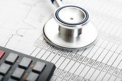 医疗保健费用的听诊器和计算器标志 免版税库存照片